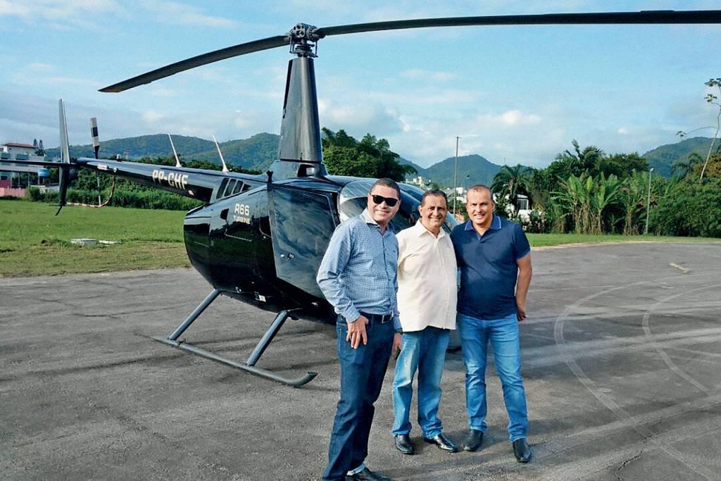 Eurípedes posando para foto com o helicoptero que comprou com dinheiro do partido.